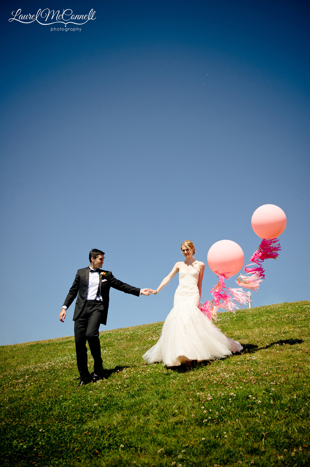 Sunny wedding portrait of bride and groom with geronimo balloons.