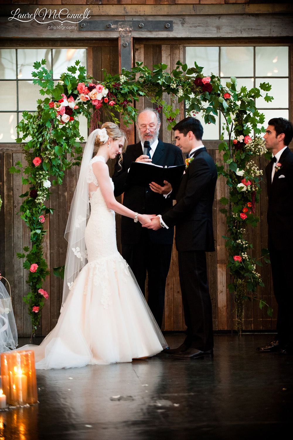 Beautiful wedding ceremony under floral archway at Seattle's Sodo Park.