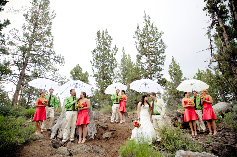 Bridal party portrait with umbrellas for outdoor rainy day wedding.