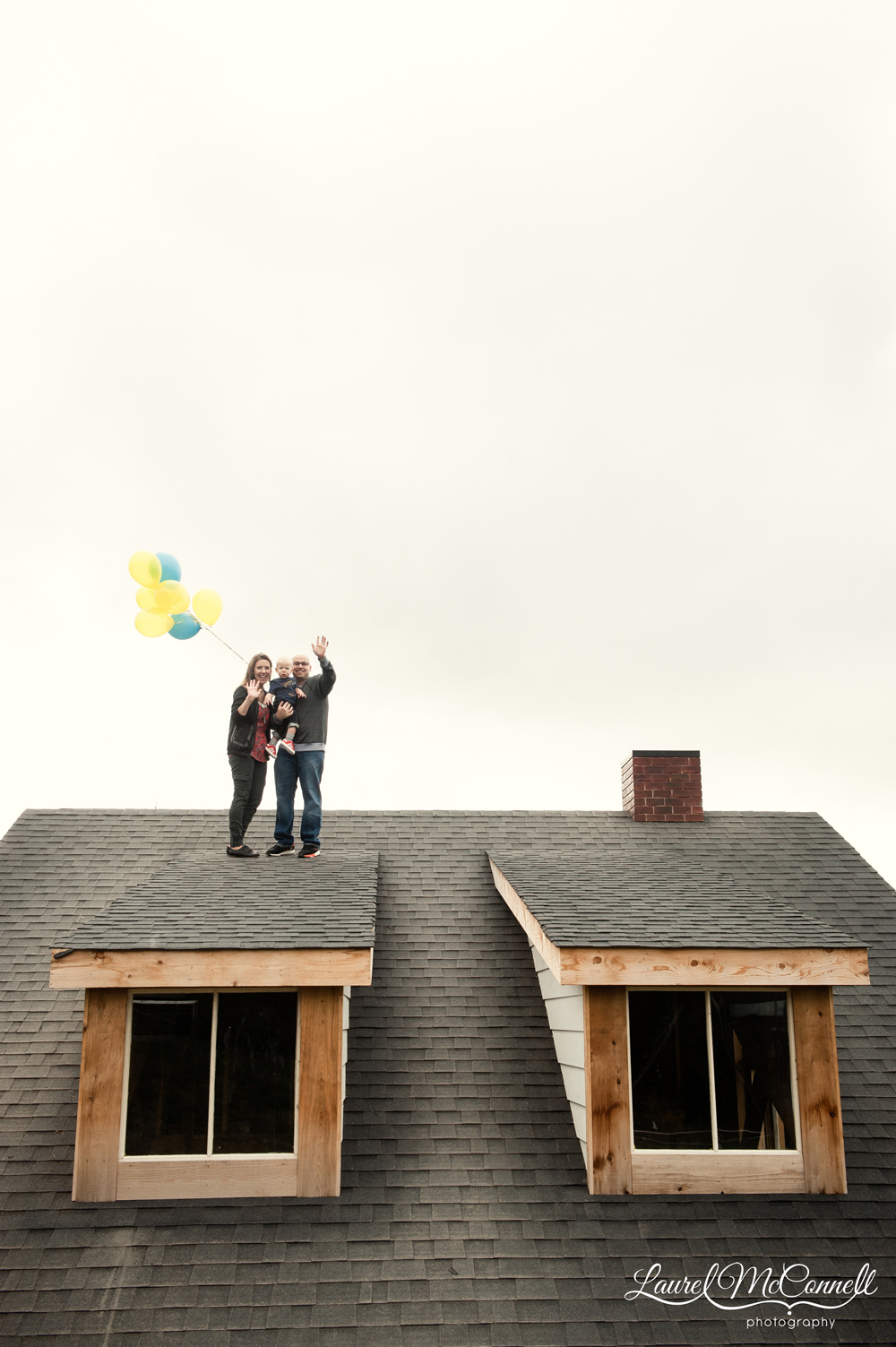 Fun portrait of family on roof with balloons.
