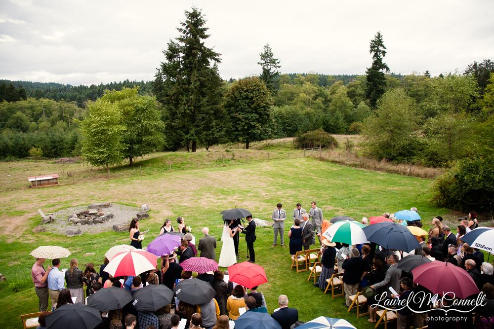 Rainy day wedding ceremony umbrellas Pacific Northwest.
