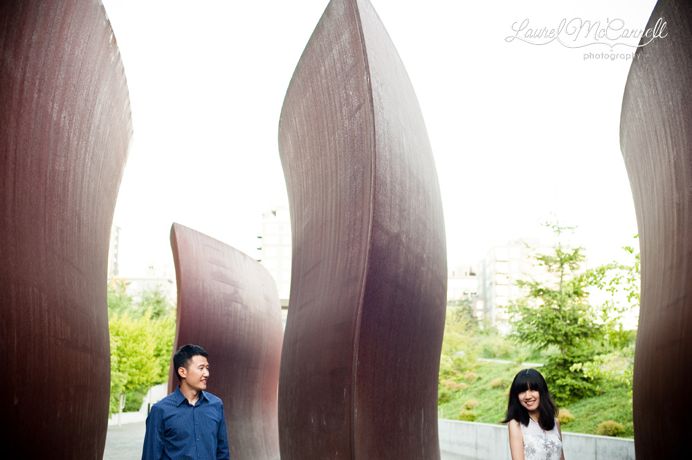 Modern engagement photos among scultures at the Seattle Art Museum's Olympic Sculpture Park.