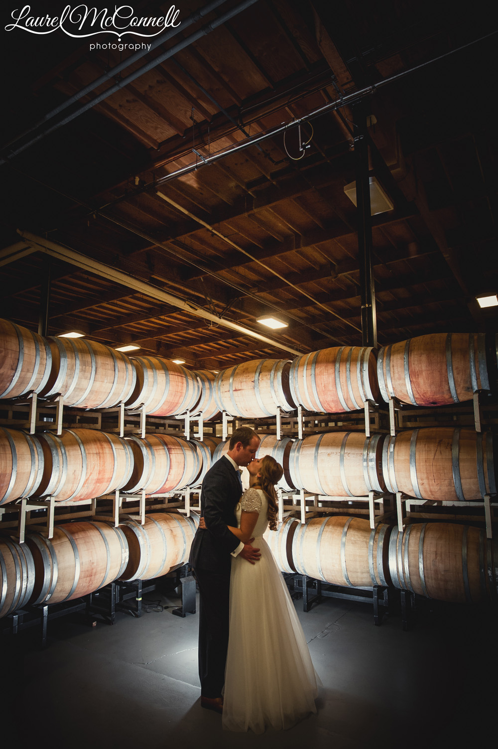 Bride and groom portrait amongst wine barrel's at Columbia Winery near Seattle, Washington photographed by Laurel McConnell Photography.