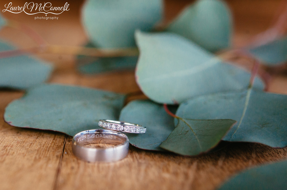 Custom engraved wedding bands with sage greenery on wine barrel photographed by Laurel McConnell Photography.