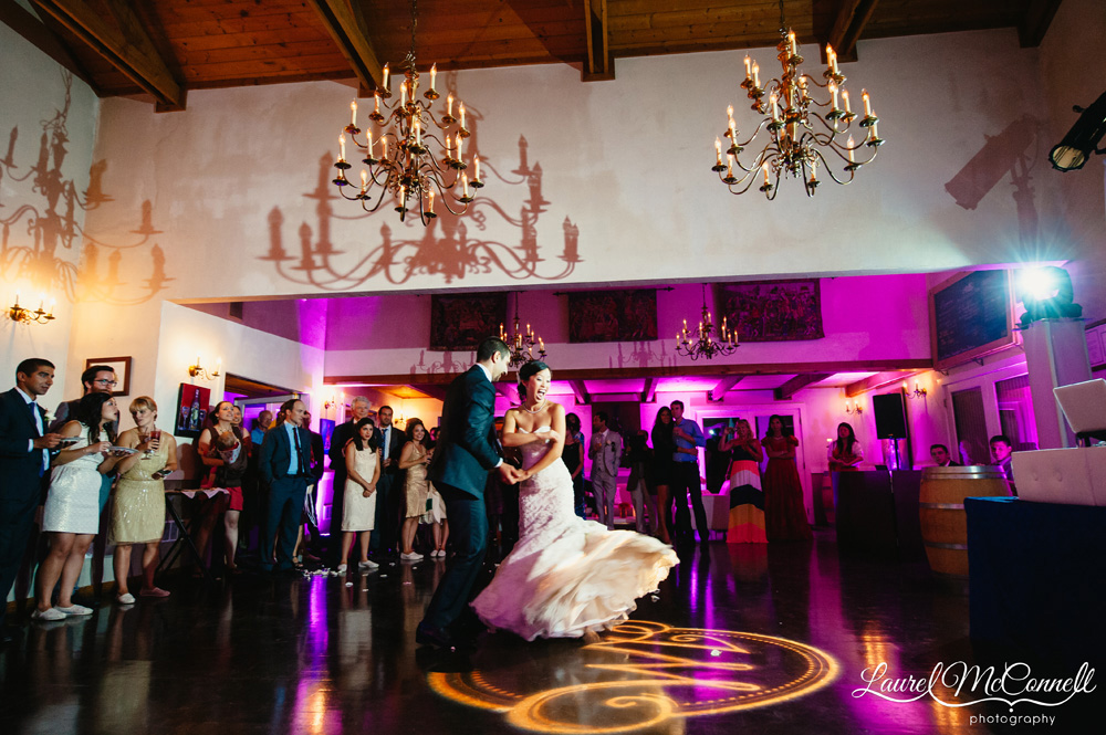 First dance at Delille Cellars with wedding logo monogram and candelabra chandeliers photographed by Laurel McConnell Photography.