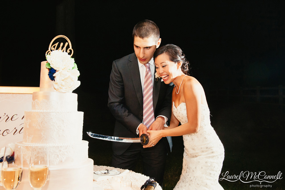 cutting wedding cake with sword sparkly winery wedding featured on wedding 13304
